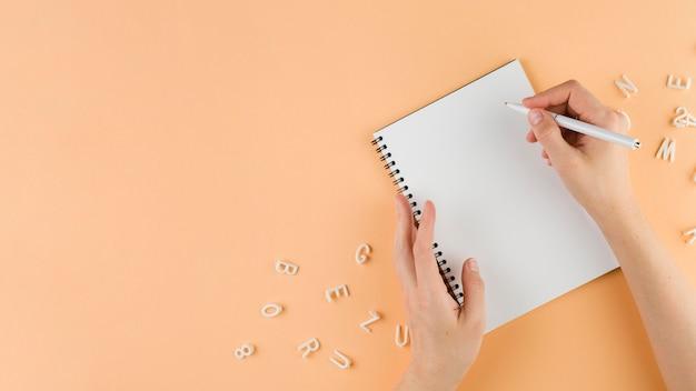 Vista superiore della scrittura a mano nel taccuino sulla scrivania con spazio di copia Foto Gratuite