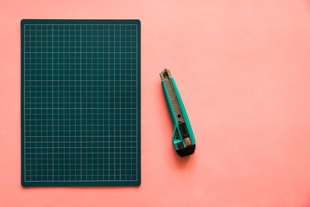 Vista superiore della stuoia di taglio di gomma verde con la taglierina verde sopra il fondo rosa della carta di colore Foto Premium