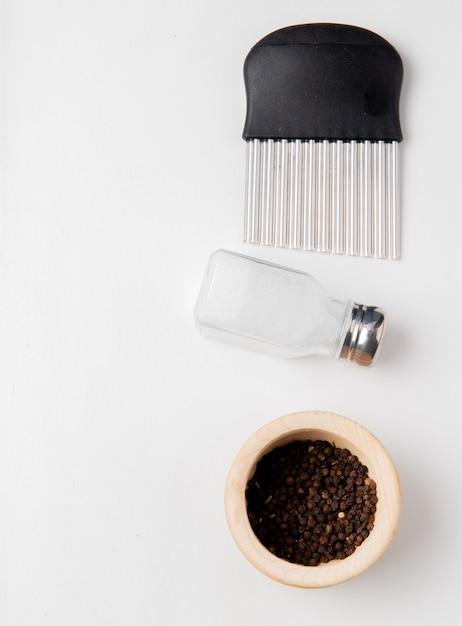 Vista superiore della taglierina della patatina fritta con i semi del pepe nero e del sale su superficie bianca con lo spazio della copia Foto Gratuite