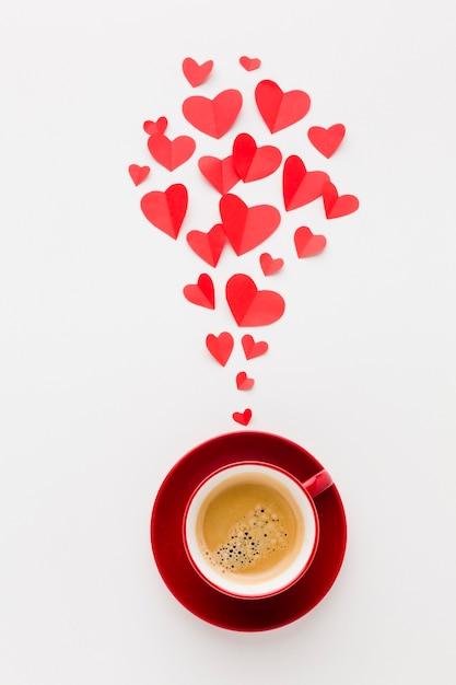 Vista superiore della tazza di caffè con forme di cuore di carta di san valentino Foto Gratuite