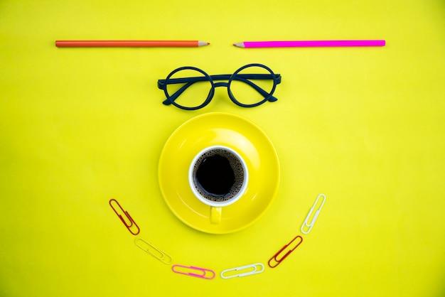 Vista superiore della tazza di caffè gialla con i vetri dell'insegnante e la matita variopinta Foto Premium