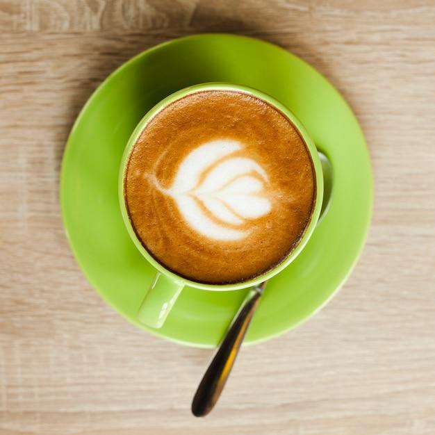 Vista superiore della tazza di caffè verde con bella arte del latte sopra superficie di legno Foto Gratuite