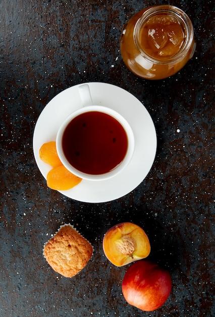 Vista superiore della tazza di tè con l'uva passa sulla bustina di tè e sull'inceppamento della pesca del bigné delle pesche su superficie nera e marrone Foto Gratuite