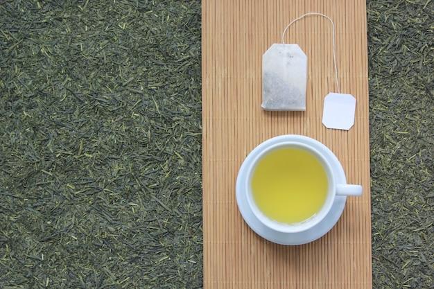 Vista superiore della tazza di tè con la bustina di tè sul fondo secco delle foglie di tè Foto Premium