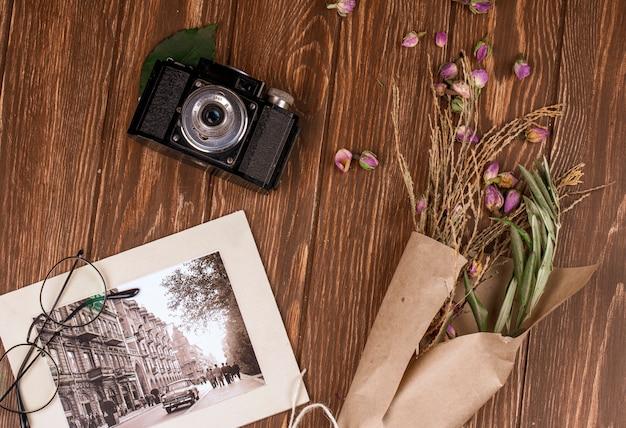 Vista superiore della vecchia macchina fotografica di vetro e della foto con i rami asciutti di colore bianco in carta del mestiere e germogli rosa asciutti sparsi su legno Foto Gratuite
