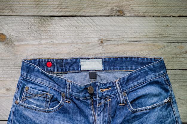 Vista superiore delle blue jeans su superficie di legno. concetto di bellezza, moda e shopping Foto Premium