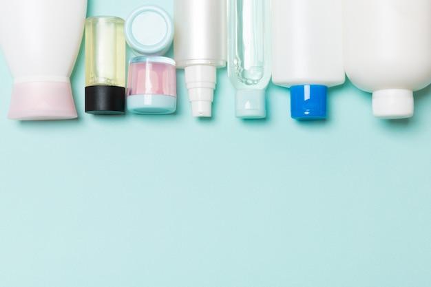 Vista superiore delle bottiglie dei cosmetici su fondo blu Foto Premium