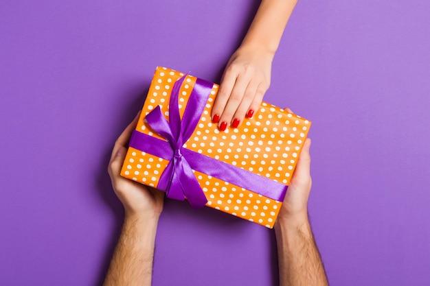 Vista superiore delle coppie che danno e che ricevono un regalo su fondo variopinto. concetto romantico con spazio di copia Foto Premium