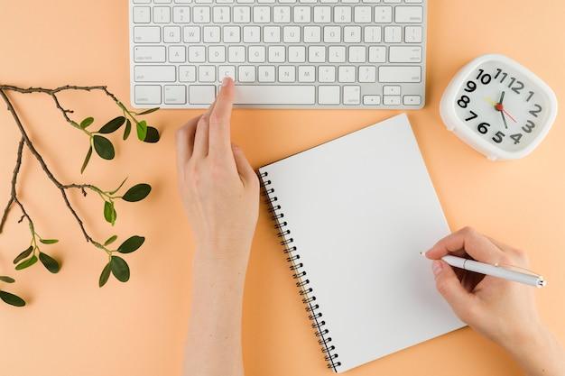 Vista superiore delle mani con il taccuino sullo scrittorio e sulla tastiera Foto Gratuite