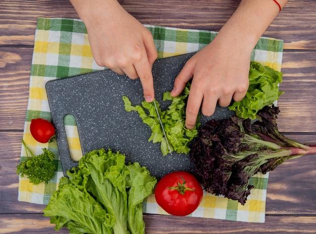 Vista superiore delle mani della donna che tagliano lattuga con il basilico del coltello sul tagliere e pomodori sul panno e sulla superficie di legno Foto Gratuite