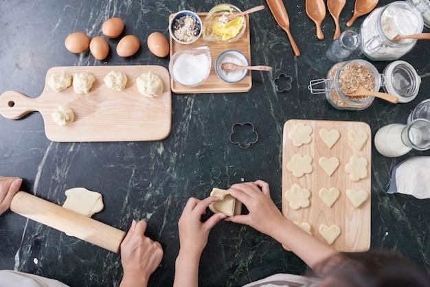 Vista superiore delle mani di due persone che cucinano insieme biscotti fatti in casa Foto Gratuite