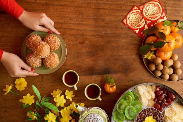 Vista superiore delle mani femminili potate che servono i piatti che preparano per la celebrazione del nuovo anno Foto Gratuite