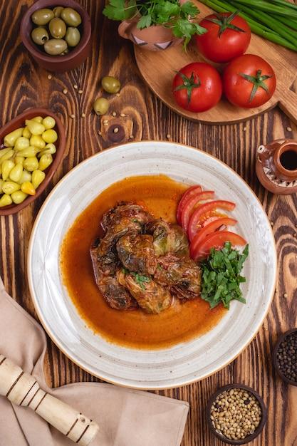 Vista superiore delle olive di verdi di pomodoro della carne dei rotoli di cavolo Foto Gratuite