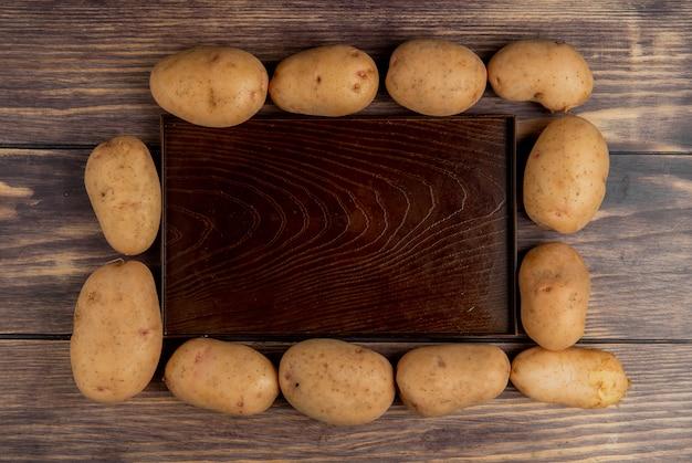 Vista superiore delle patate intorno al vassoio vuoto su superficie di legno Foto Gratuite