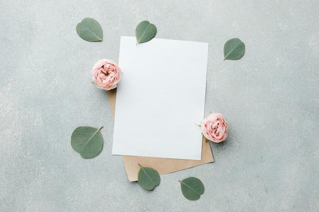 Vista superiore delle rose e delle foglie con le carte in bianco Foto Gratuite