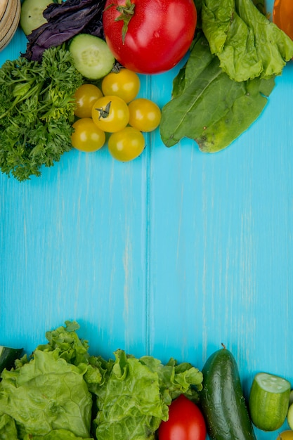 Vista superiore delle verdure come cetriolo della lattuga degli spinaci del pomodoro del basilico del coriandolo sulla superficie del blu con lo spazio della copia Foto Gratuite