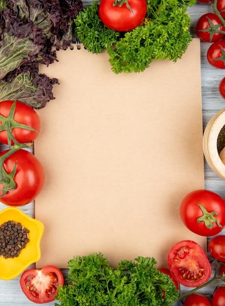 Vista superiore delle verdure come coriandolo del pomodoro del basilico con il frantoio di aglio e del pepe nero con il blocco note su superficie di legno con lo spazio della copia Foto Gratuite