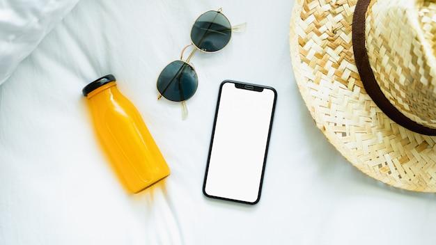 Vista superiore dello schermo vuoto di smartphone in camera e cappello, occhiali, durante il tempo libero. Foto Premium