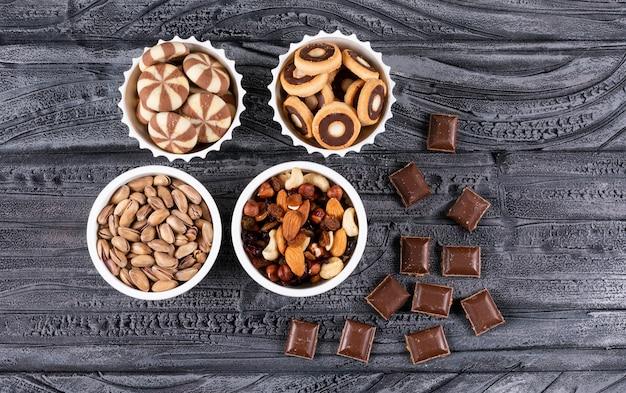 Vista superiore di diversi tipi di snack come noci, biscotti e cioccolato in ciotole su superficie scura orizzontale Foto Gratuite