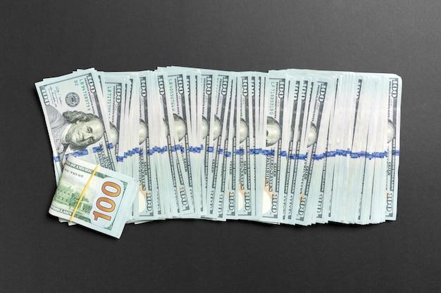 Vista superiore di mentire 100 banconote in dollari in una riga su sfondo colorato. chiuda in su del concetto di risparmio di denaro Foto Premium