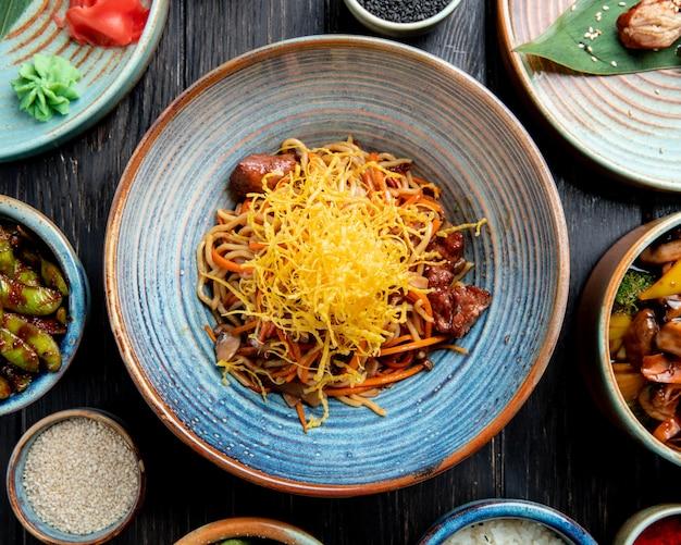 Vista superiore di mescolare le tagliatelle fritte con manzo e verdure in un piatto sulla tavola di legno Foto Gratuite
