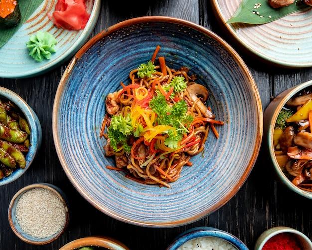 Vista superiore di mescolare le tagliatelle fritte con verdure e gamberi in un piatto sul tavolo di legno Foto Gratuite