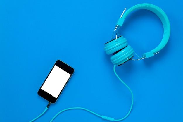 Vista Superiore Telefono Cellulare E Cuffie Su Sfondo Blu Con Spazio