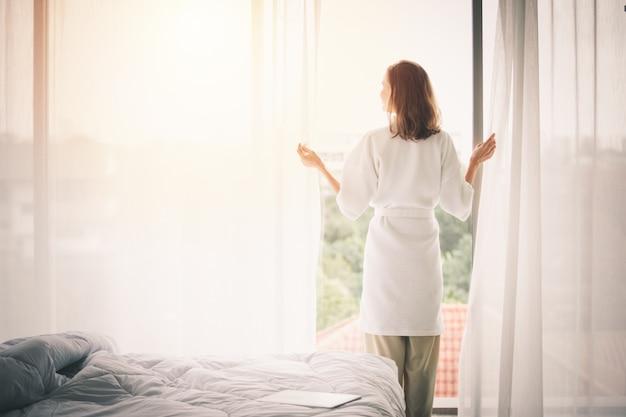 Visualizza indietro le tende di apertura della donna in una camera da letto bianca Foto Premium