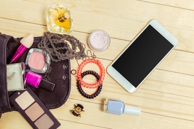 Visualizza su roba di borsa donna su legno Foto Premium