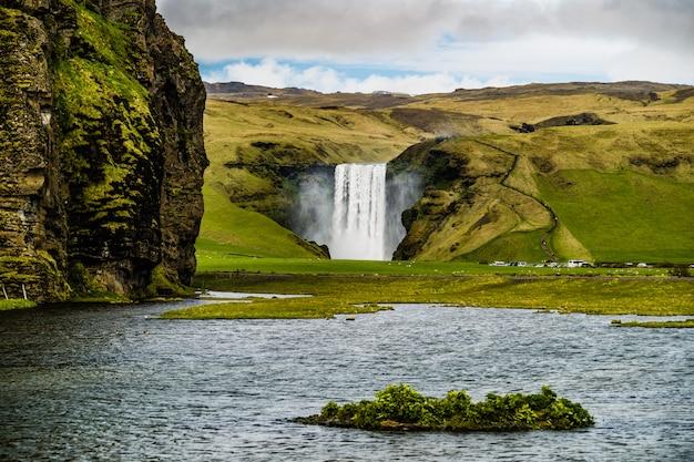 Visualizza su un potente flusso di cascata skogafoss, islanda Foto Premium