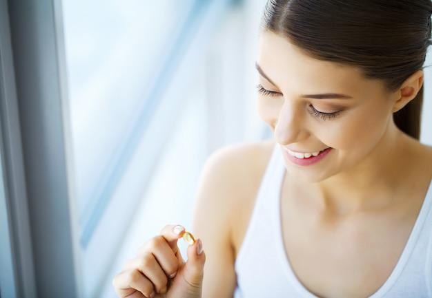 Vitamine. mangiare sano. ragazza felice con la capsula dell'olio di pesce omega-3. concetto di dieta sana. Foto Premium