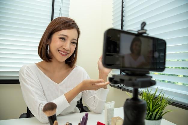 Vlogger di bellezza donna asiatica o blogger in diretta in diretta di tutorial trucco cosmetico Foto Premium