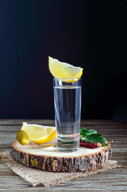 Vodka o tequila in bicchierini e in bottiglia con salsa di limone su fondo di legno rustico. Foto Premium
