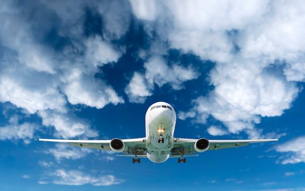 Volo dell'aeroplano dell'aereo di linea del passeggero nelle nuvole bianche del cielo Foto Premium
