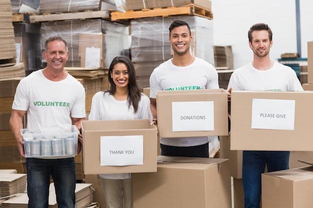 Volontari che sorridono alle scatole di donazioni della tenuta della macchina fotografica Foto Premium