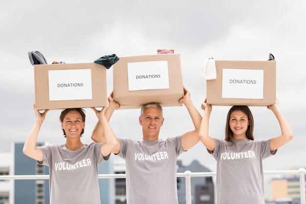 Volontari felici che trasportano scatole di donazione sulla loro testa Foto Premium