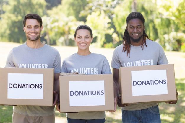 Volontari felici con le scatole di donazione in parco Foto Premium