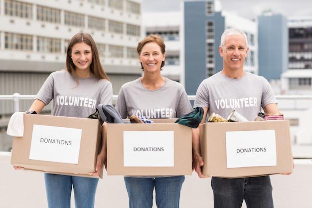 Volontari sorridenti che tengono le scatole di donazione Foto Premium