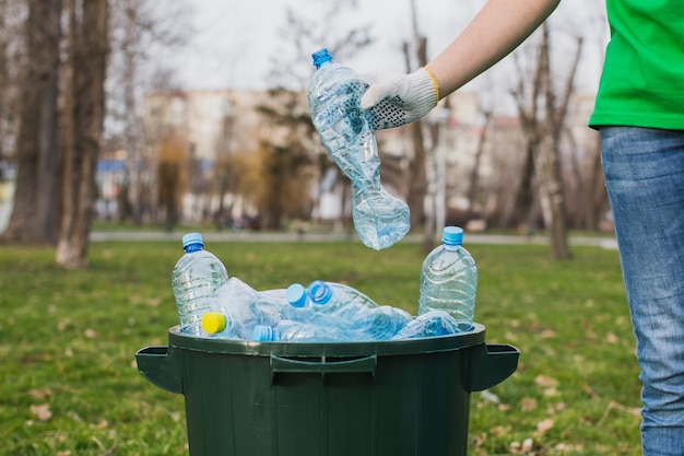 Volontario mettendo bottiglie di plastica nel cestino Foto Gratuite