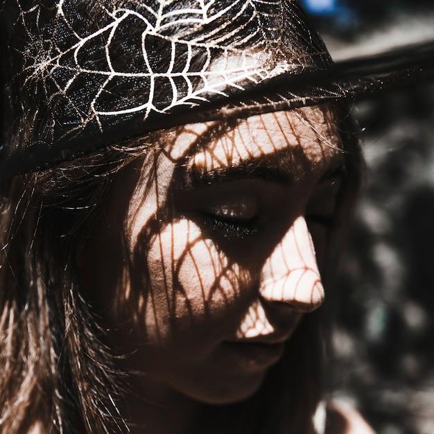 Volto di giovane donna in cappello da strega chiudendo gli occhi Foto Gratuite