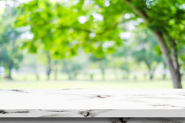 Vuoto tavolo di marmo bianco su sfocatura sfondo verde parco, montage di visualizzazione del prodotto Foto Premium