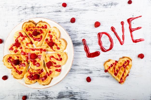 Waffle belga a forma di cuore su bianco Foto Premium