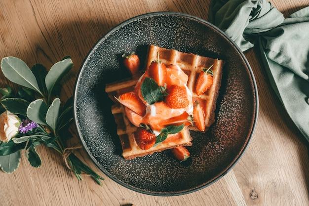 Waffle belgi con frutti di bosco, gelato e cioccolato. impostazione del tavolo per la colazione. stile di vita mattutino. Foto Premium