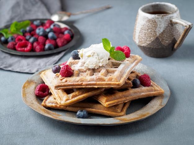 Waffle belgi con lamponi, sciroppo di cioccolato. prima colazione con tè su sfondo scuro, vista laterale Foto Premium