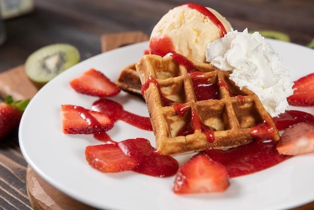 Waffle con fragole, gelato alla vaniglia e panna montata Foto Gratuite