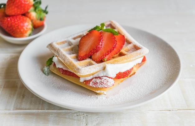 Waffle con fragole su legno Foto Premium
