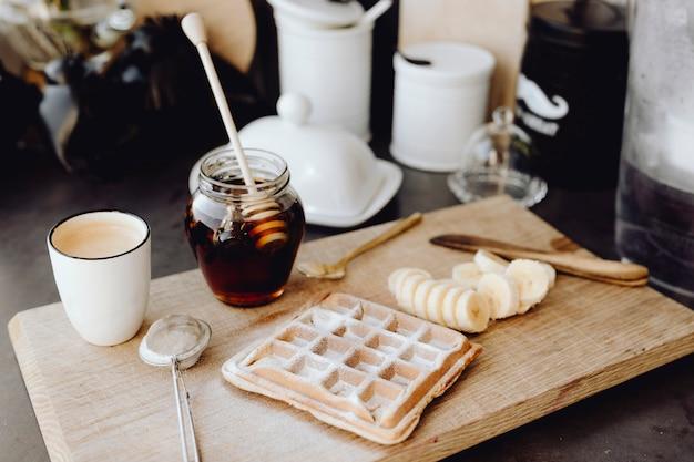 Waffle e fette di banana su un vassoio di legno accanto a un barattolo di miele Foto Premium
