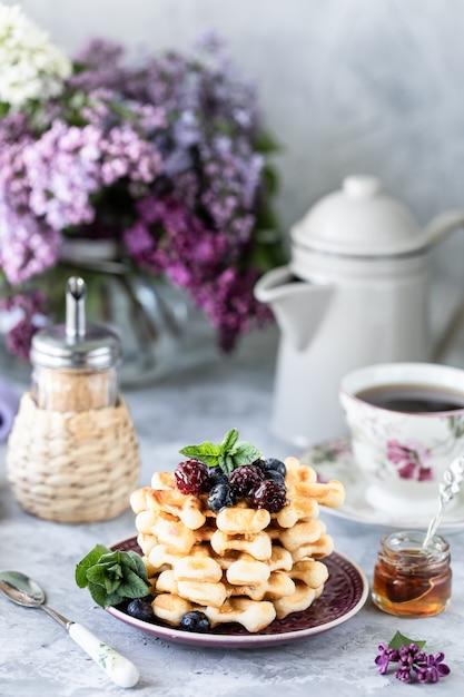 Waffle fatti in casa con frutti di bosco e miele, una tazza di caffè sul tavolo con un mazzo di lillà. Foto Premium