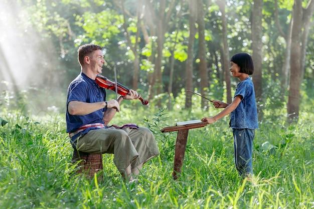 Western uomo che suona il violino con ragazze tailandesi Foto Premium