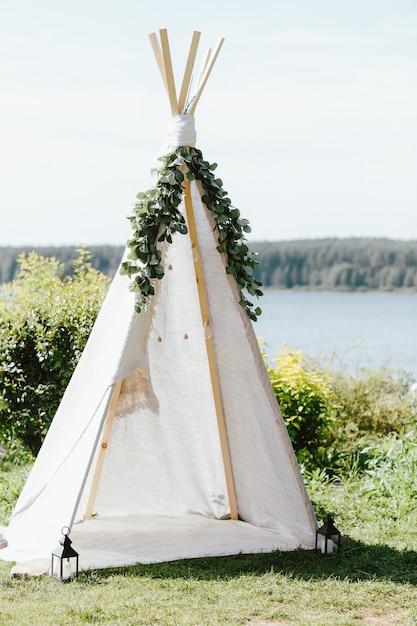 Wigwam in tessuto di legno decorato con rami di eucalipto verde nel cortile Foto Premium